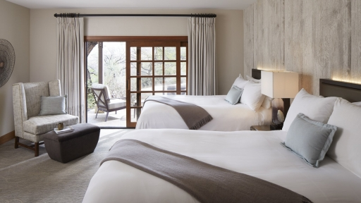 View of guest bedroom with two queen beds and balcony at Miraval Arizona.