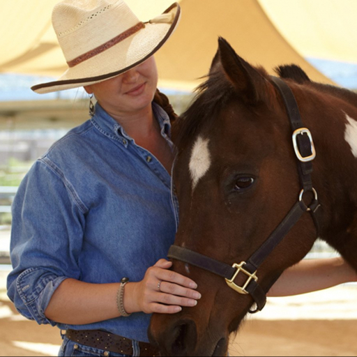woman caring for horse after a ride